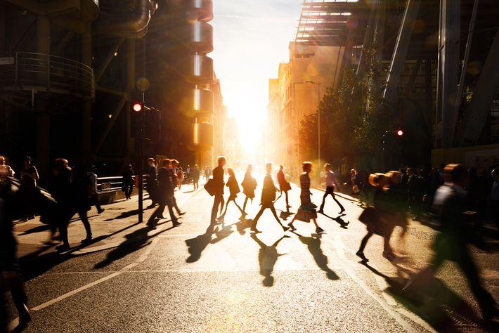 Pessoas atravessam as ruas de uma cidade inglesa ao amanhecer.