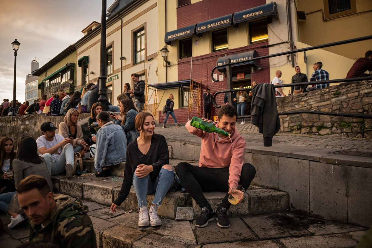 À noite, os habitantes locais socializam em torno do antigo porto de Gijón, um ponto de ...