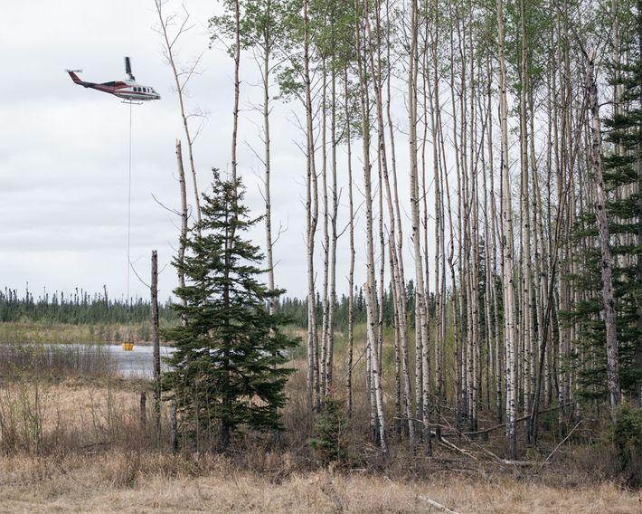 Um helicóptero recolhe água para combater um incêndio.