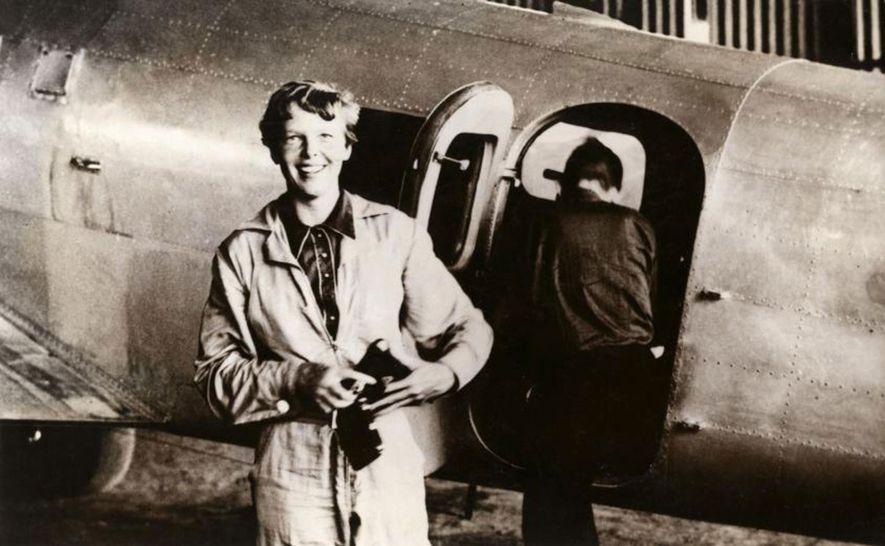 Amelia Earhart junto ao seu Lockheed Electra, no aeroporto de Parnamirim, no Brasil, em junho de 1937. O navegador Fred Noonan está em segundo plano.