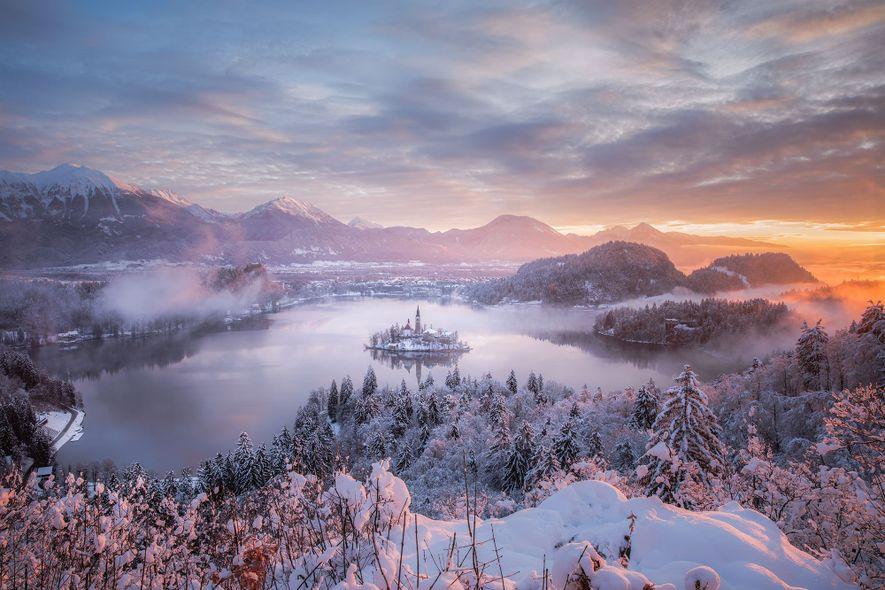 A neve sobre o lago Bled, na Eslovénia, confere à cena uma aura de conto de ...