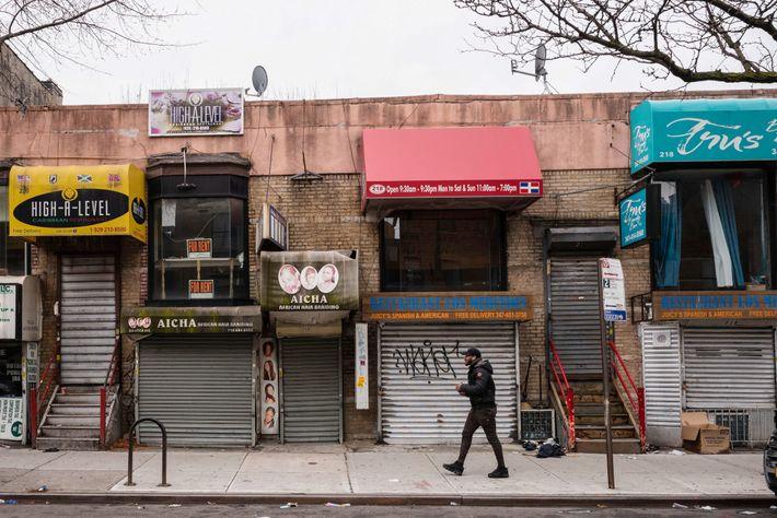No bairro de Crown Heights, em Brooklyn, Nova Iorque, uma pessoa passa por uma fileira de ...