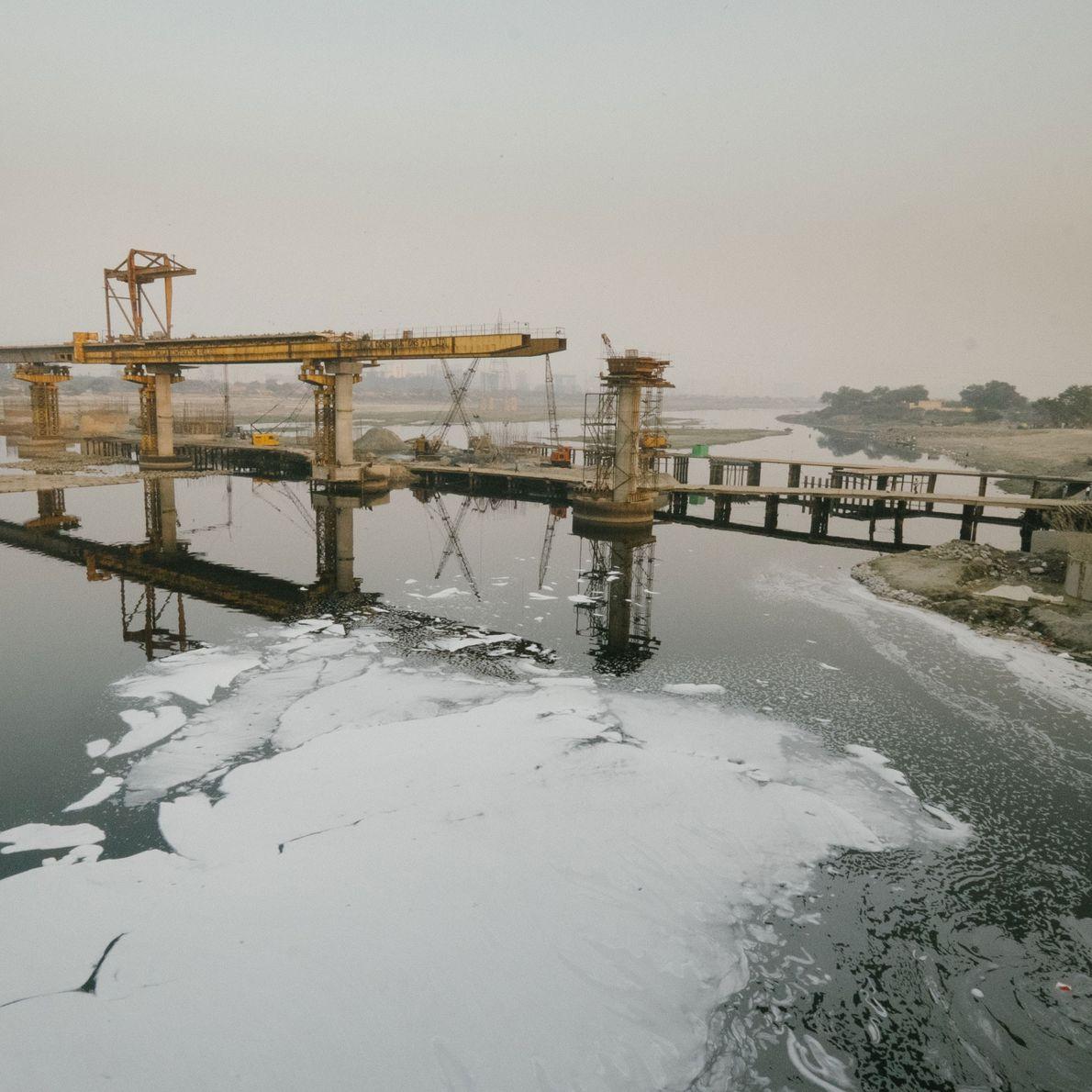 Fotografia de projetos de construção sobre o poluído Rio Yamuna, em Deli.