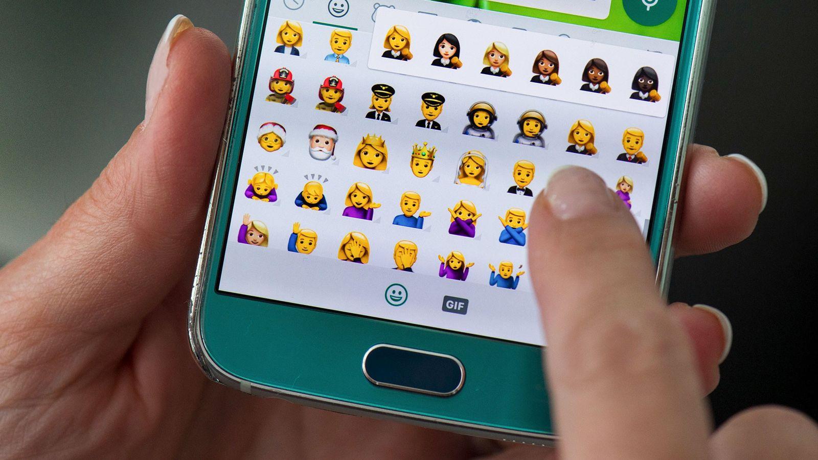 Utilizador a escrever mensagens de emojis num smarphone
