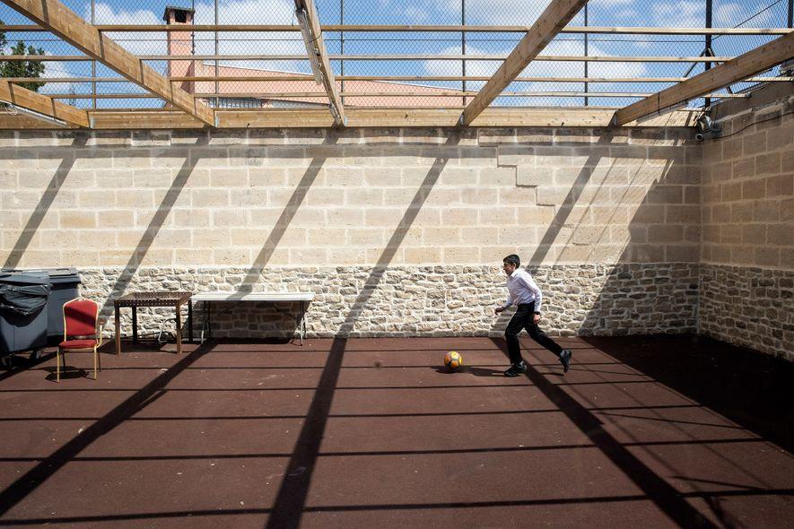 Um rapaz judeu brinca no pátio da Grande Sinagoga de Sarcelles, um subúrbio da classe operária ...