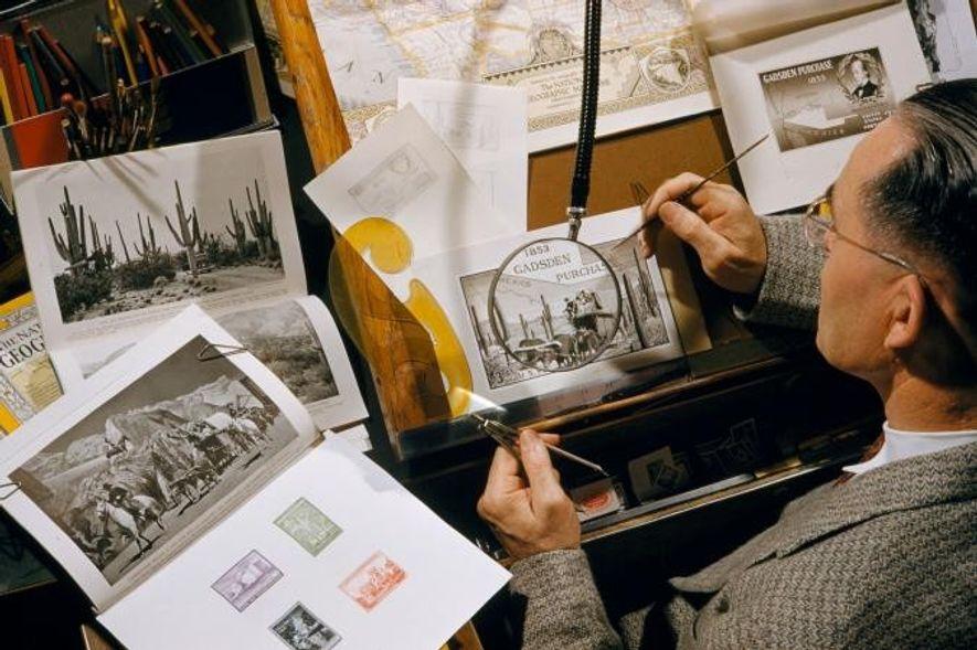 Um funcionário do governo observa, através de uma lupa, o desenho de uma antiga revista de …