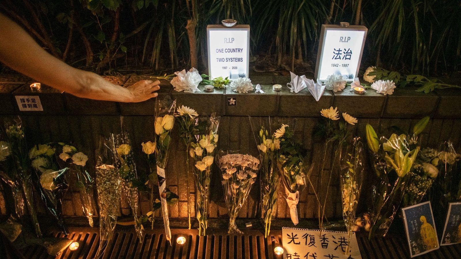 Uma mulher acende uma vela num memorial improvisado em Hong Kong para homenagear a morte de ...