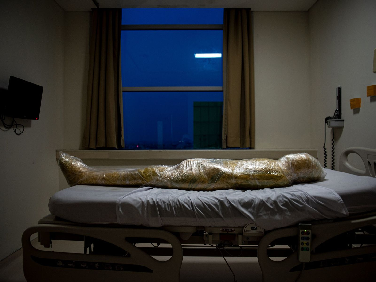 O corpo de uma vítima suspeita de COVID-19 jaz num hospital indonésio. Após a morte do ...