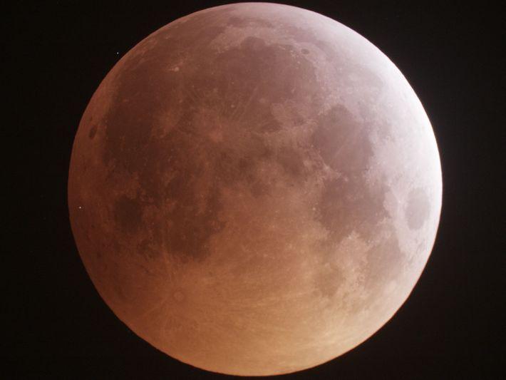 Um ponto de luz brilhante, no lado esquerdo da lua, mostra o momento de impacto de ...
