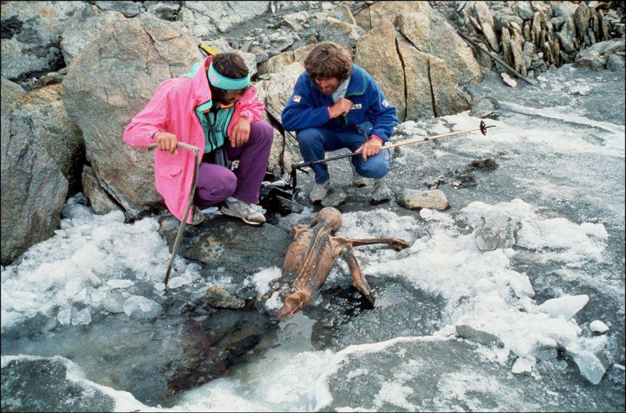 O alpinista Reinhold Messner, à direita, e o seu colega inspecionam os restos mumificados de Ötzi, ...