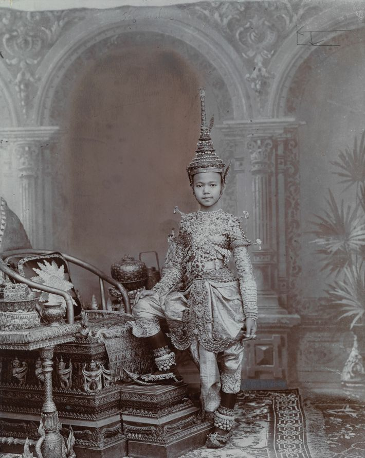 Um príncipe siamês usa uma indumentária repleta de joias, incluindo um capacete com a forma de ...