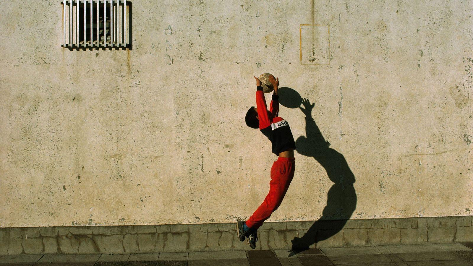 Um guarda-redes salta e estende os braços para tentar agarrar a bola.