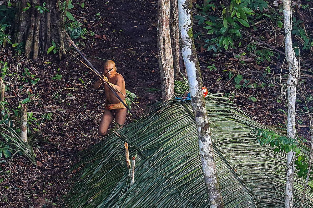 Imagem de indígena na Amazónia, no Brasil, a apontar uma flecha