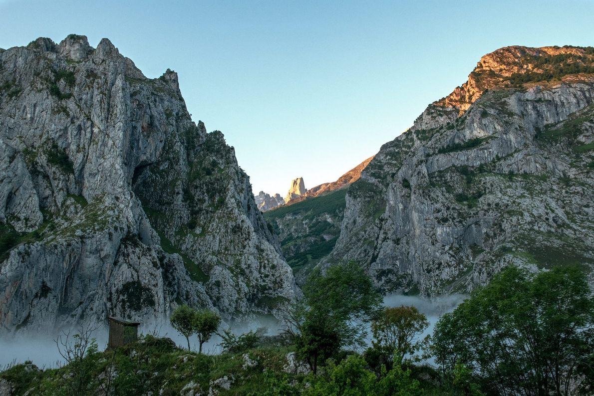 O sol a erguer-se sobre os picos de Naranjo de Bulnes, também conhecido como Picu Urriellu, ...