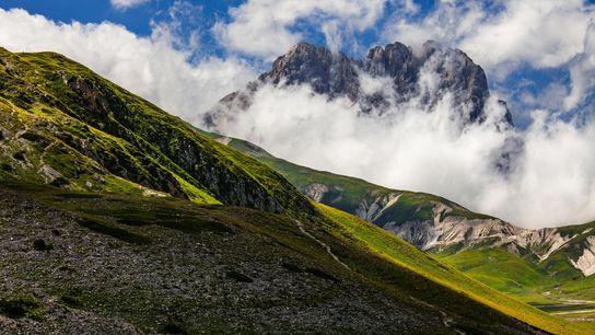 O Corno Grande, o pico mais alto das montanhas dos Apeninos, destaca-se entre as nuvens. De ...
