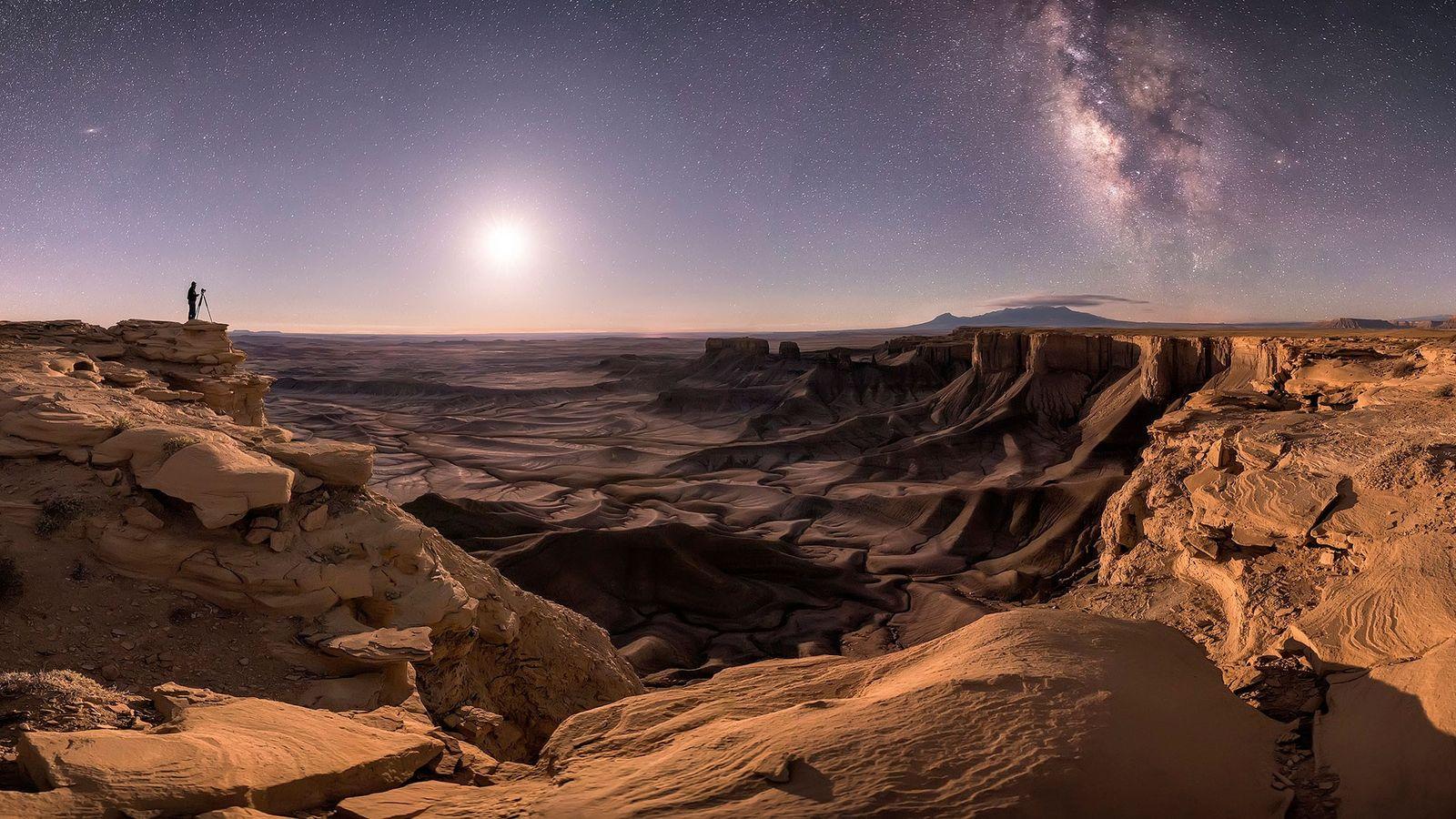 Um fotógrafo solitário aguarda em Moab, Utah, com a sua silhueta em contraste com o céu ...