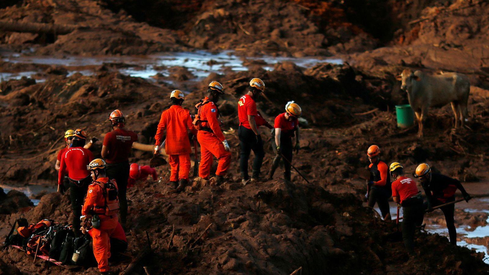 Membros de uma equipa de salvamento procuram vítimas, depois do colapso de uma barragem de resíduos.