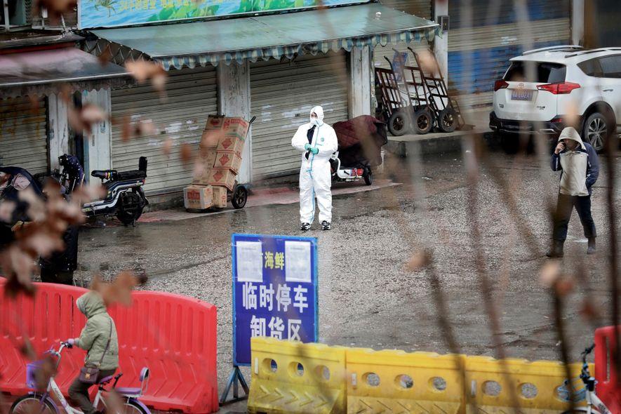 Um trabalhador com equipamento de proteção no mercado de peixe agora encerrado em Wuhan, na China, ...
