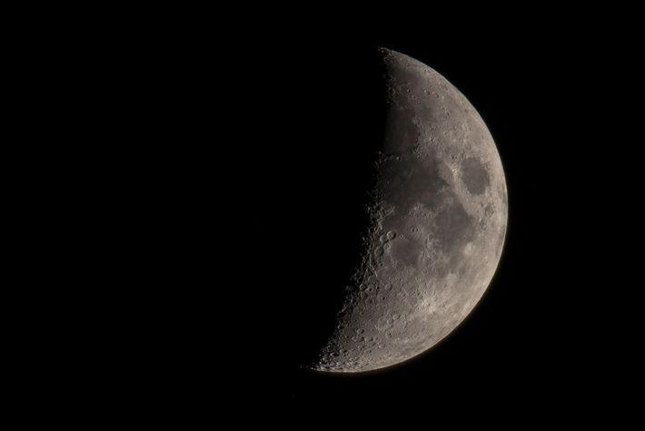 Uma vista de telescópio da lua revela muitas das crateras bem preservadas e as planícies escuras ...