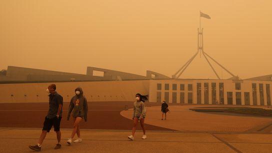 Visitantes da Casa do Parlamento, em Canberra, com máscaras faciais devido ao fumo dos incêndios florestais ...