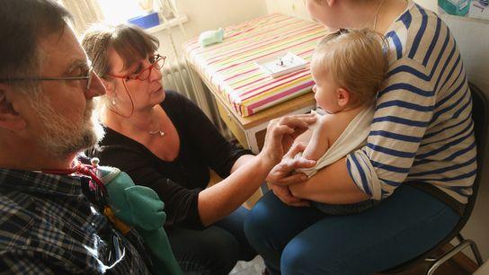 Uma assistente de saúde prepara Tijana, de 11 meses, para levar a vacina contra o sarampo, ...