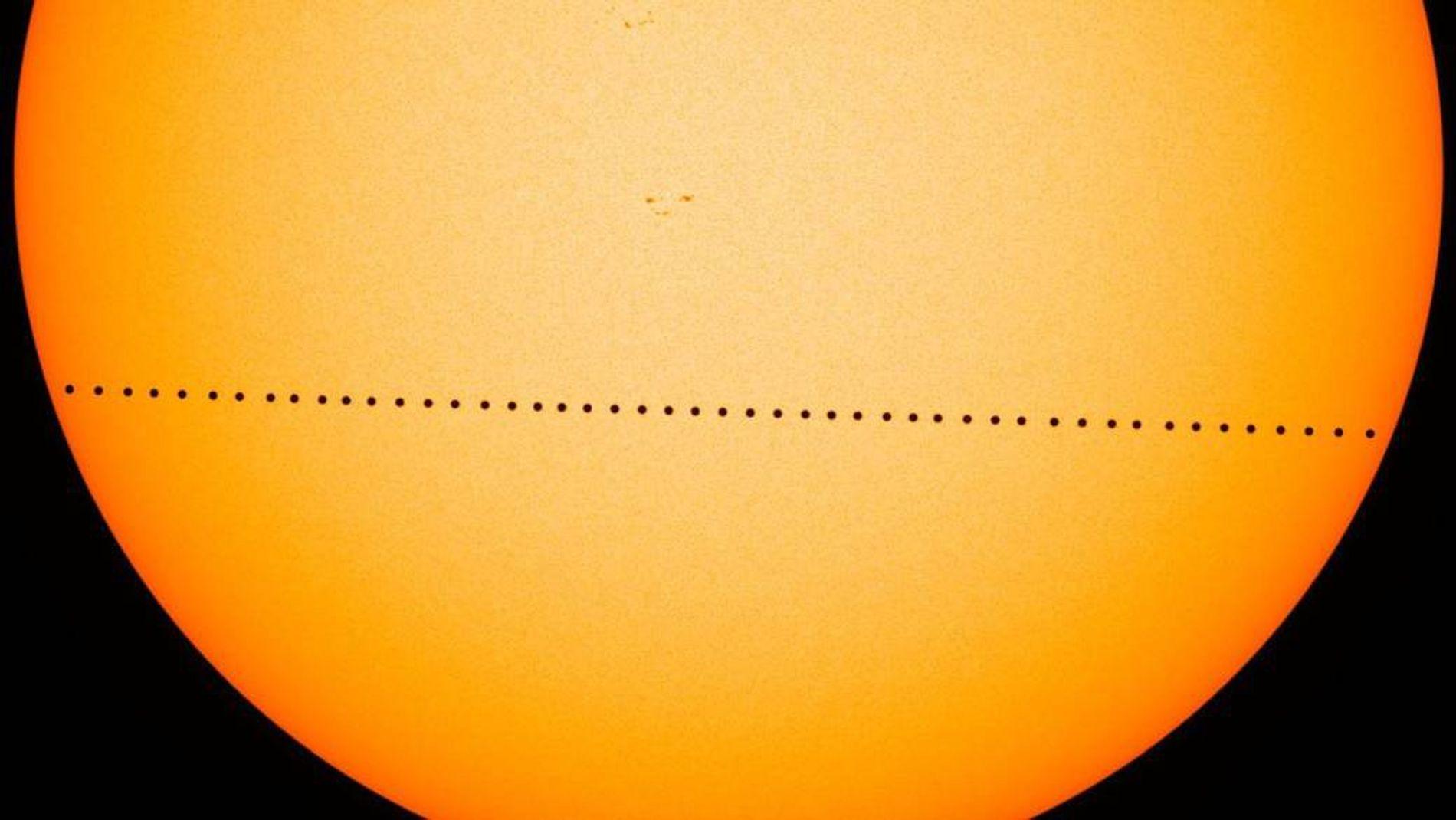 O pontilhado a negro representa Mercúrio a atravessar o disco solar, numa imagem composta durante o ...