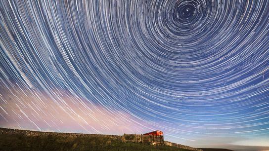 Uma composição fotográfica descreve o movimento circular aparente das estrelas.
