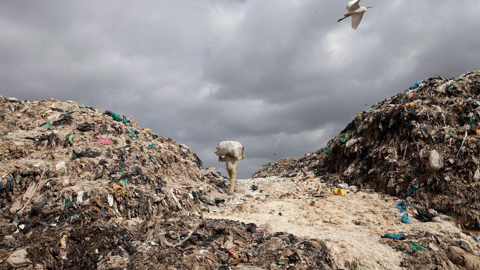 Um homem transporta uma saca com materiais recicláveis, no aterro de Dandora, um dos maiores e ...