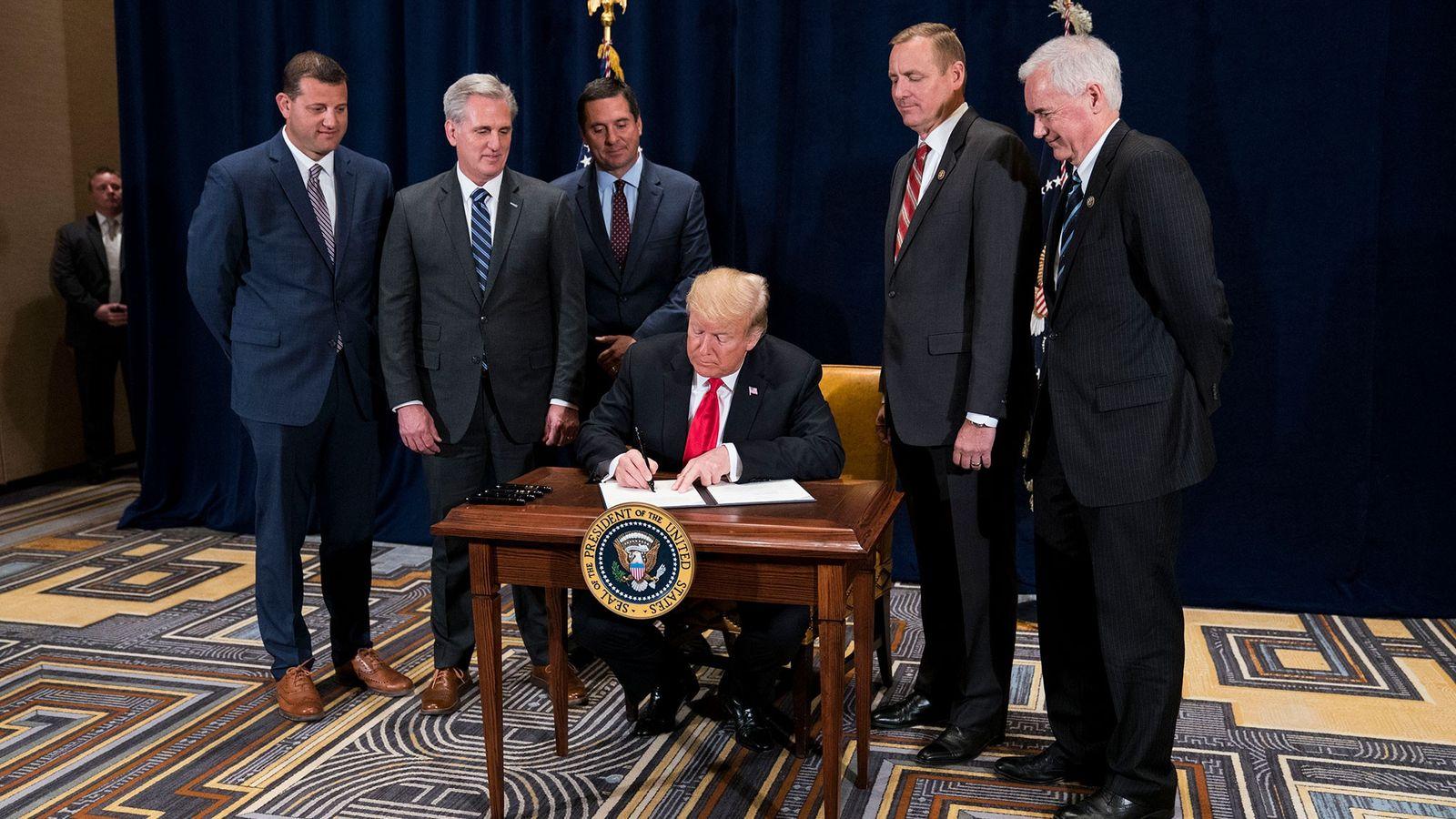 """O presidente Donald Trump assina um memorando presidencial para """"minimizar encargos reguladores desnecessários"""", a 19 de ..."""