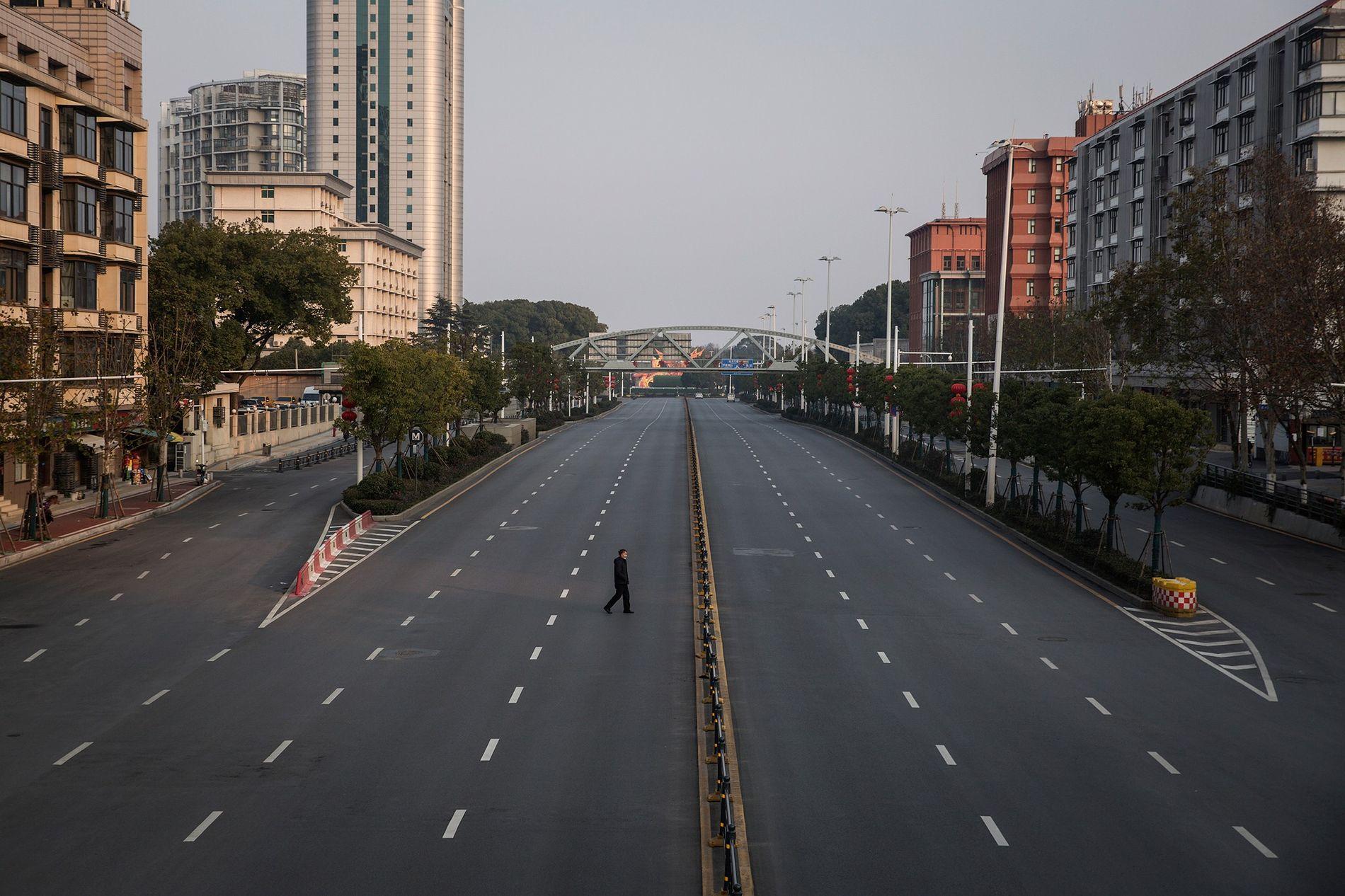Um homem atravessa uma estrada deserta, no dia 3 de fevereiro de 2020, em Wuhan, na ...
