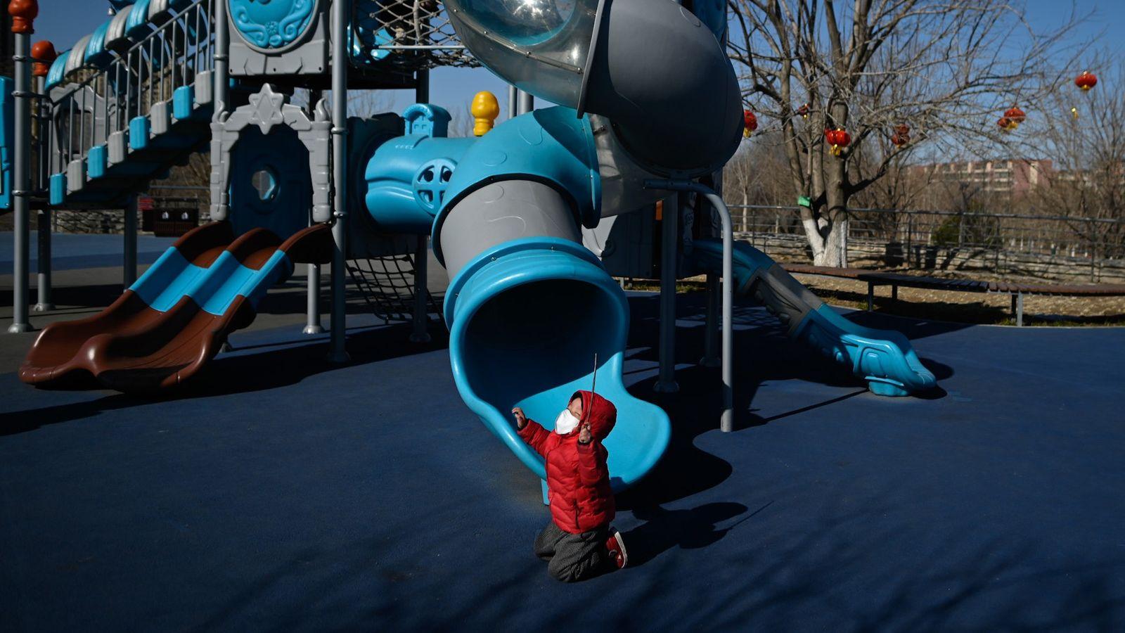 Um menino como uma máscara de proteção a brincar num parque em Pequim, na China.