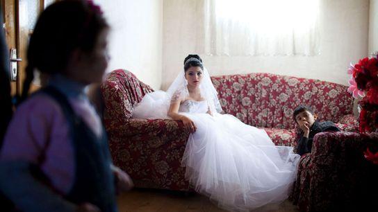 Imagem de uma noiva adolescente sentada num sofá com padrão floral