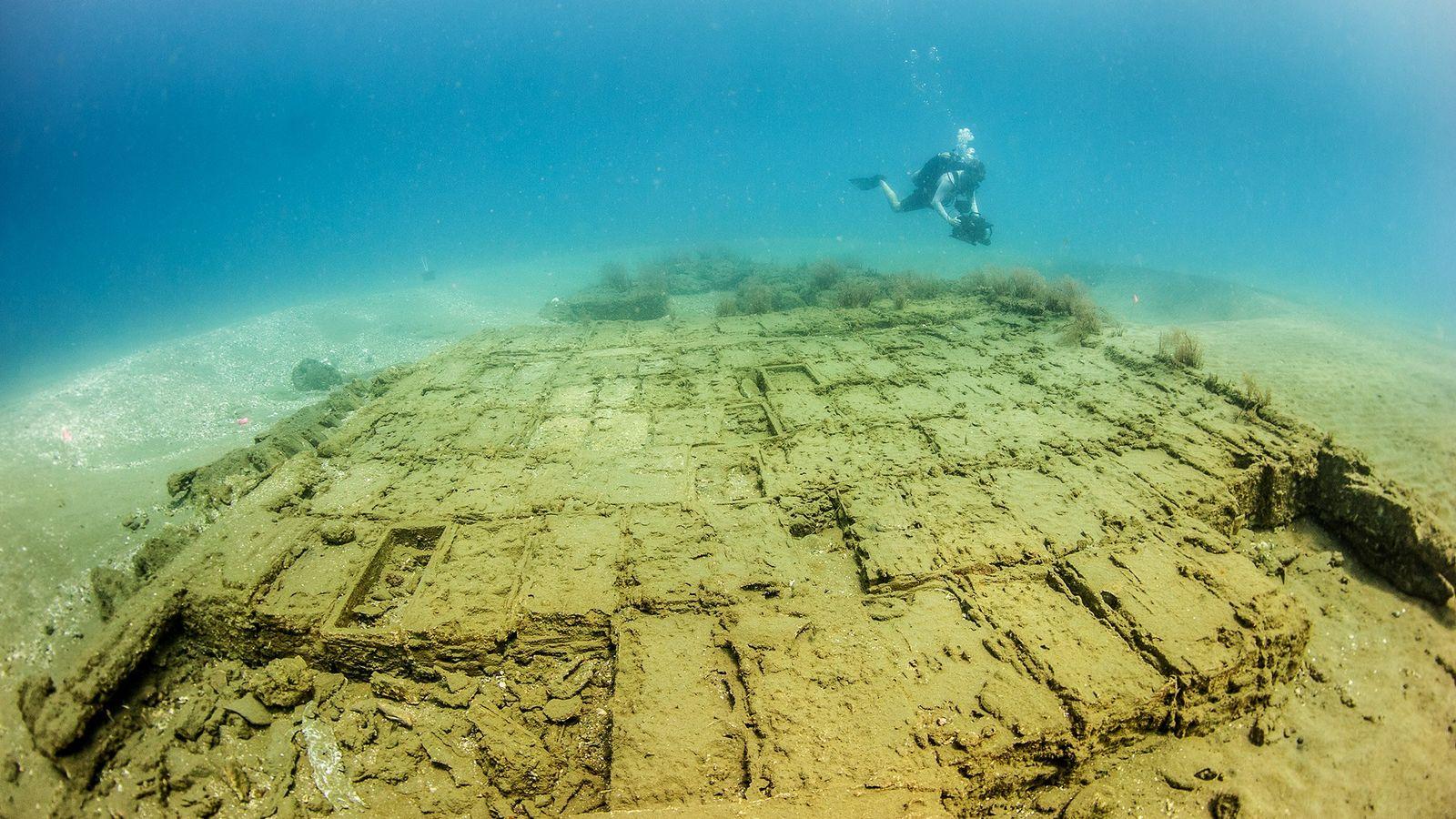 Um mergulhador inspeciona caixas de madeira num naufrágio espanhol do século 17 descoberto no Panamá.