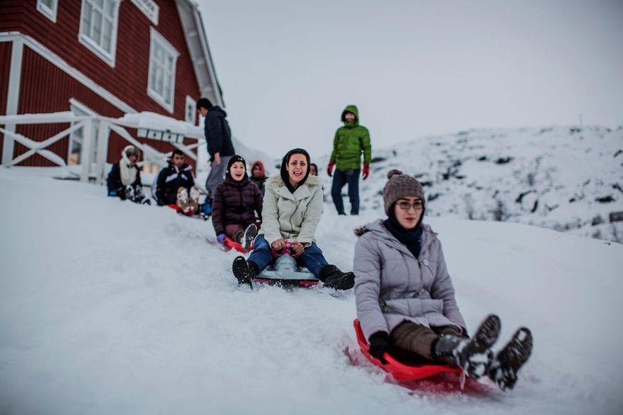 Muitos dos refugiados em Riksgränsen nunca tinham visto neve antes. A estância comprou trenós para ajudar ...