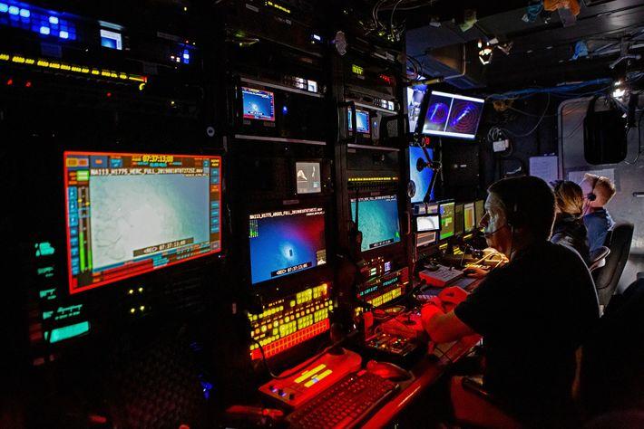 Dentro da sala de controlo, os membros da tripulação operam veículos submarinos e mantêm-se vigilantes de ...