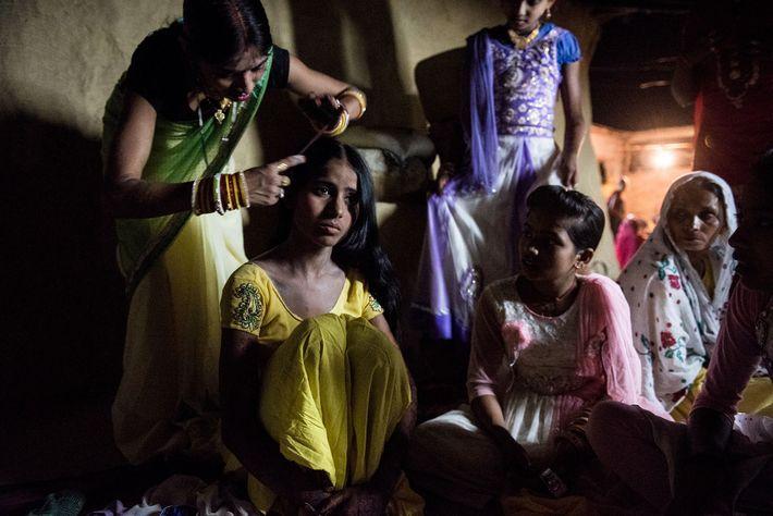 Os familiares de Muskaan ajudam-na a vestir-se para o seu casamento.