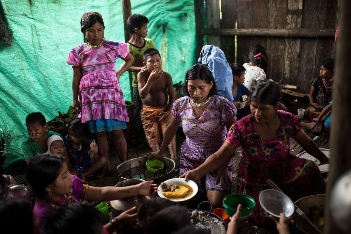 Mulheres mais velhas preparam a comida para toda a comunidade. Embora alguns aldeões tenham fugido durante …