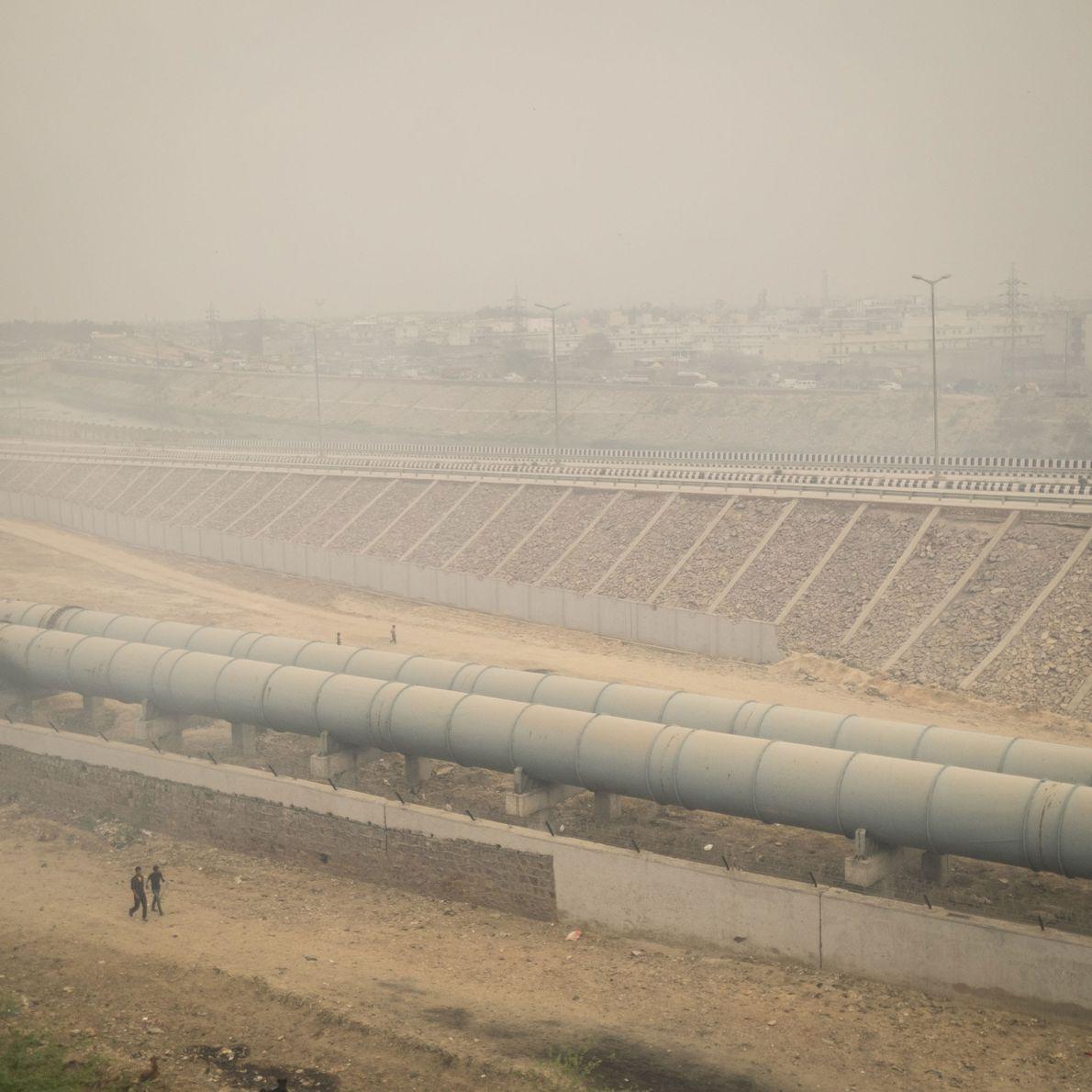 Fotografia de uma aldeia situada por baixo de uma lixeira gigante ao ar livre que queima ...