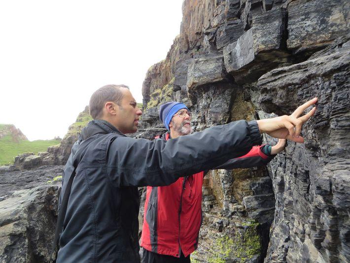 Homens examinam a superfície da falésia