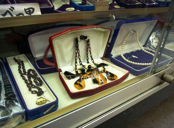 Nas ruas de Enoshima, no Japão, as lojas de souvenirs exibem peças – como este colar ...