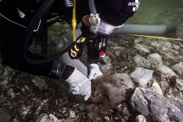Arqueólogos escavam artefactos de rituais, no Lago Titicaca, na Bolívia.