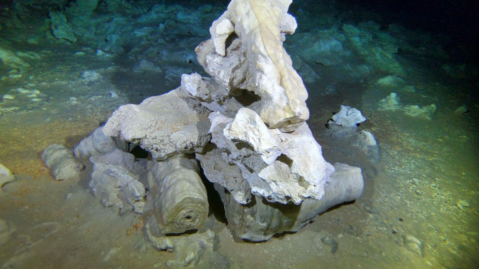 Pilhas de rochas e concreções partidas – estalactites ou estalagmites – marcam o trajeto através da ...
