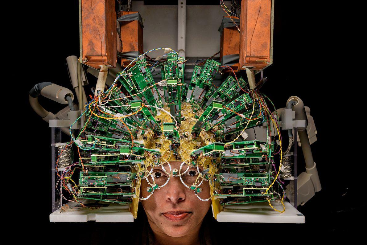 Um engenheiro com um capacete de sensores, parte de um exame cerebral, no Centro de Imagem ...
