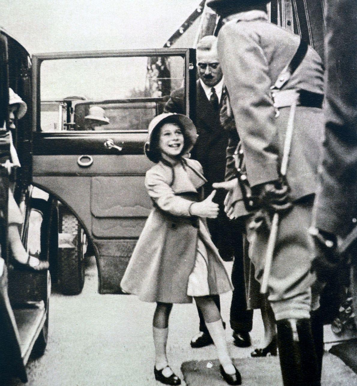 A rainha Isabel II, na altura com oito anos de idade, cumprimenta um oficial da guarda, ...