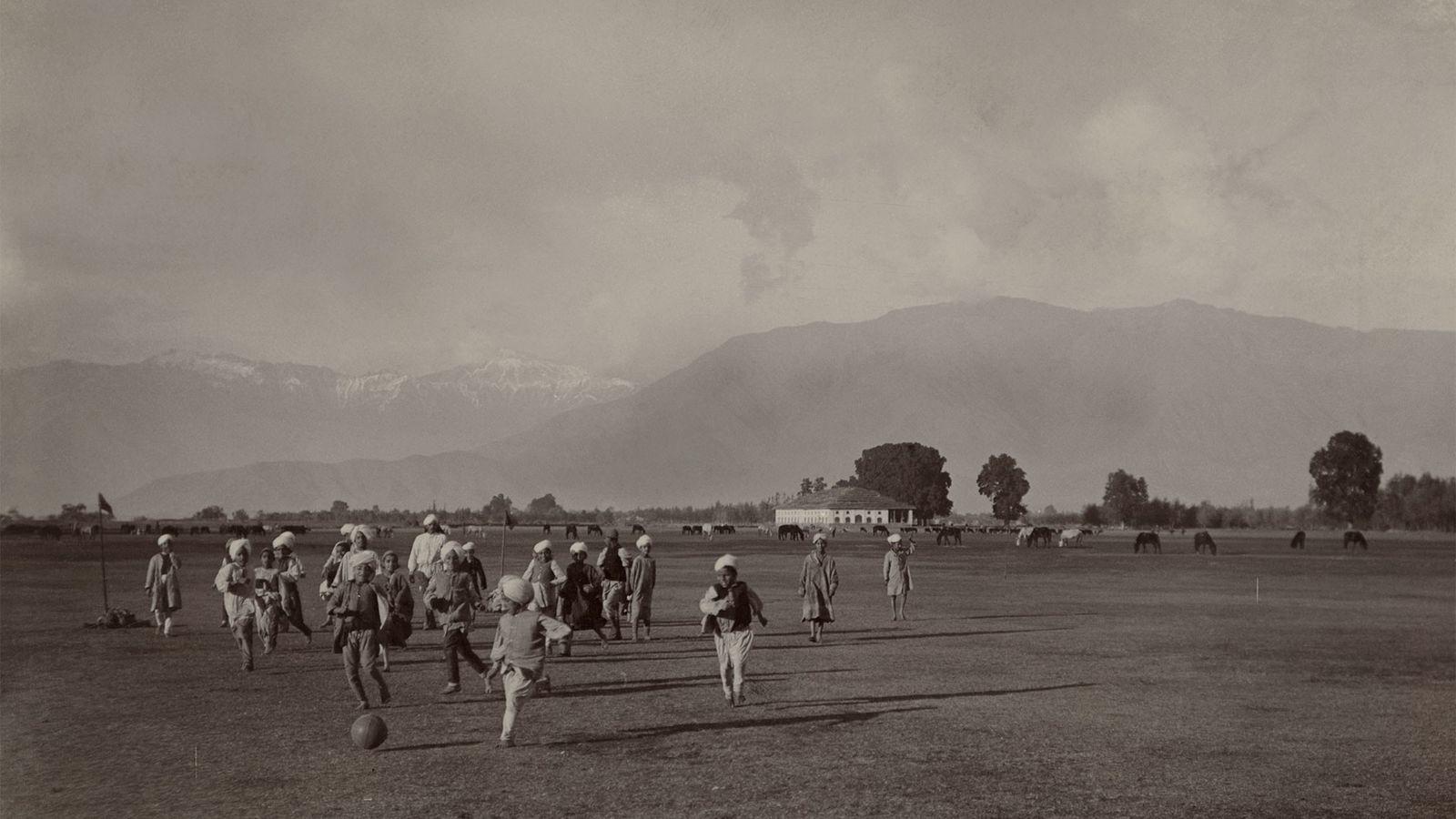 Um grupo de crianças joga uma partida de futebol espontânea.