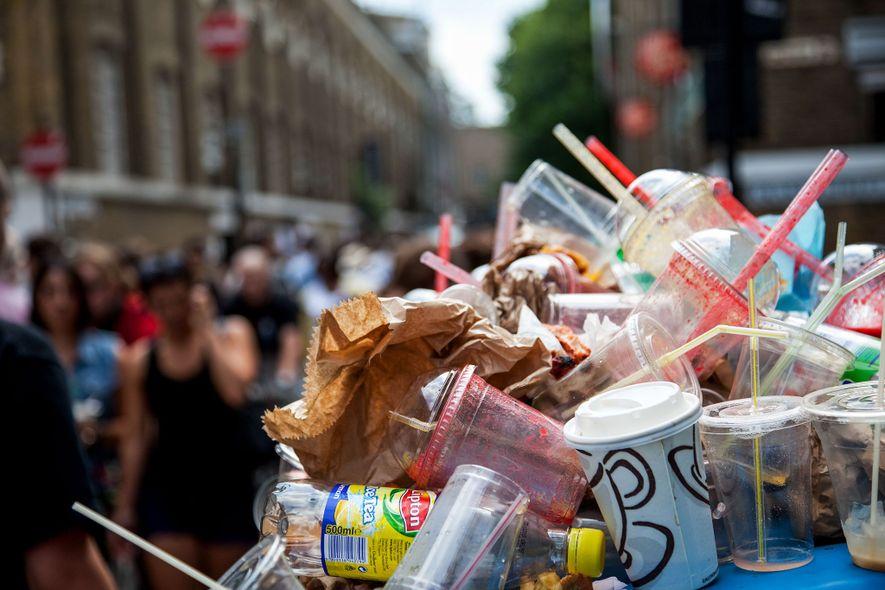 Há lixo a transbordar dos caixotes no mercado de Brick Lane, no East End de Londres. ...