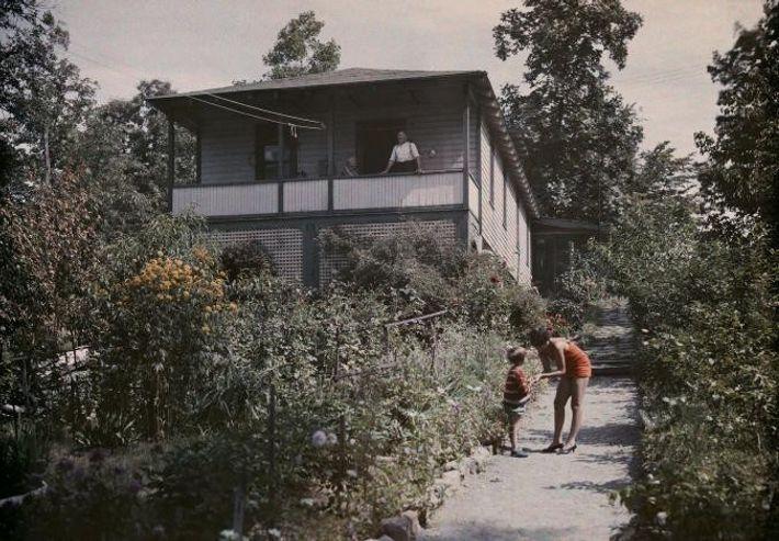 Uma mulher fala com uma criança junto a uma casa de verão.