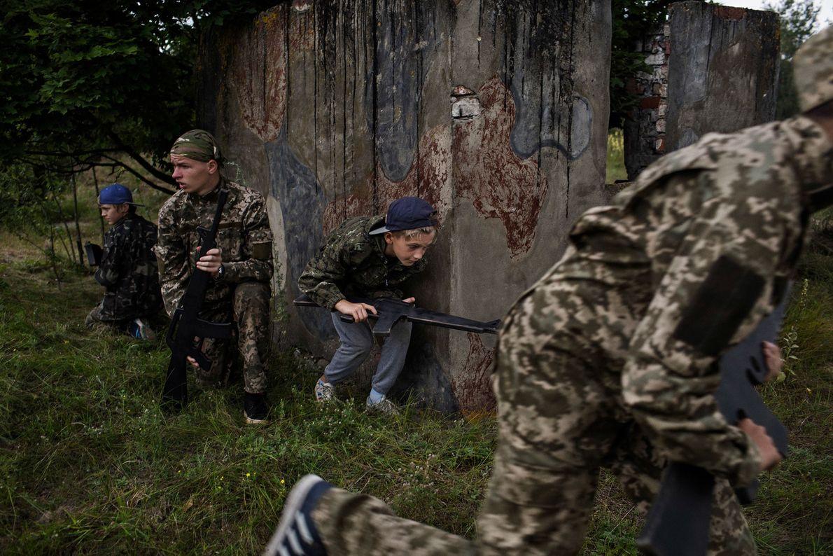 Crianças ucranianas num exercício militar de simulação de guerra, no campo RANGER.