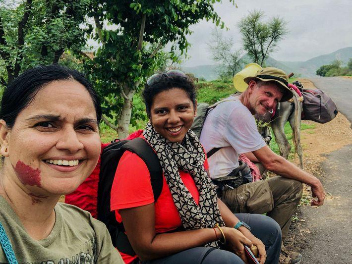 Loveleen Mann (esquerda) e Priyanka Borpujari param para descansar, com Paul Salopek, no trilho na Índia.