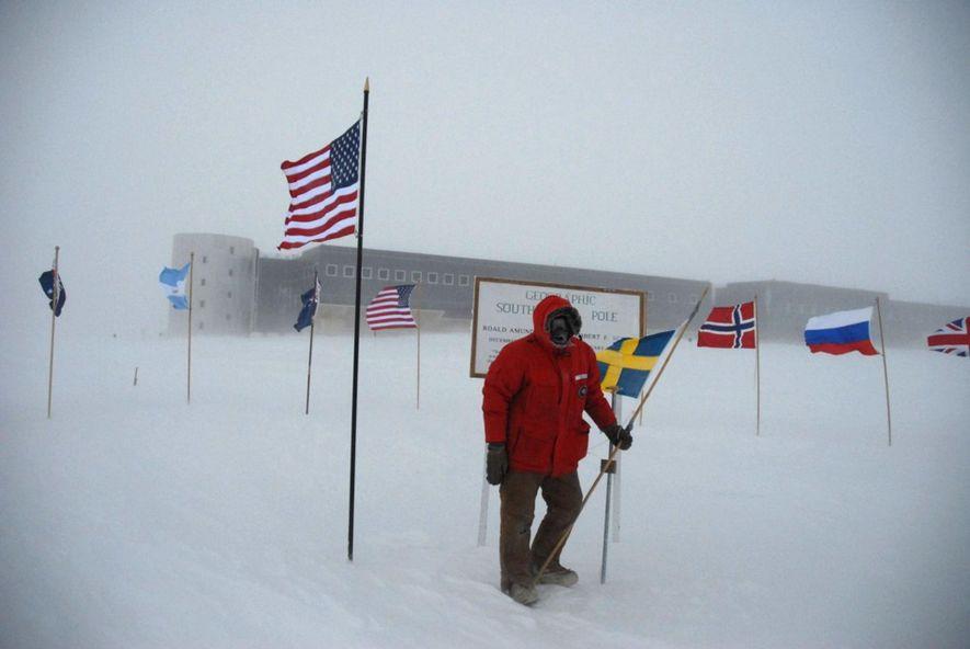 Sven Lidström no Polo Sul, com a estação Amundsen-Scott em pano de fundo.